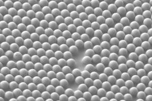 A scanning electron microscope image shows the microscale concave interface structure that was studied The material consists of microspheres partially embedded in sticky tape, forming microscale concave interfaces Credit Jacob Rada