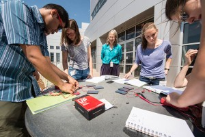 NREL researcher Sarah Kurtz center works with college students participating in the Hands-On PV Experience as they build mini solar concentrators outside of NRELs Solar Energy Research Facility during a weeklong immersion at the laboratory in Golden, CO P
