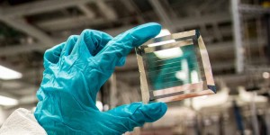 Xinjing Huang, a doctoral student in Forrests lab, holds a solar cell module with 40 transparency, based on the formula with an estimated 30-year lifetime Photo Robert CoeliusMichigan Engineering