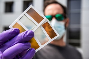 NREL researcher Lance Wheeler holds samples of perovskite-based window technology Photo by Dennis Schroeder, NREL