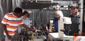 Experimental setup for a magnetometer using alkali sodium atoms in Tripathis DSU lab The yellow glow from a sodium laser is visible in the picture Left to right Lawrence Taylor, a freshman pursuing a BS in Engineering Physics Tripathi Robin Depto, a BS El