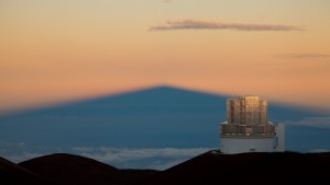 Sunrise-illuminated Subaru Telescope and shadow of Mauna Kea - Copyright Subaru Telescope
