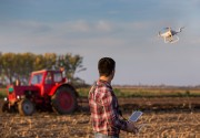 Farmer controlling drone over field