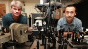 Gunter Lpke left and Wei Zhang look over their laser optics table in Lpkes Small Hall laboratory Photo by Stephen Salpukas
